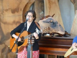 Pamela Ortiz performing with Claro Walnut Burl Stool auction item in the background.