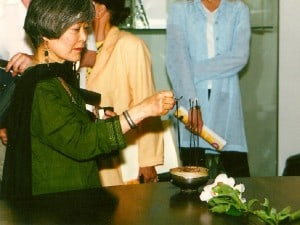 Mira Nakashima lighting incense in a Toshiko Takaezu bowl before the ceremony.