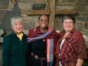 """Mira Nakashima, Naomi Tutu, and Irene Goldman at the Nakashima Foundation for Peace Arts Building in front of George Nakashima's Sanskrit name, """"Sundarananda"""" carved on a cross by Nakashima's grandson Satoru Amagasu."""
